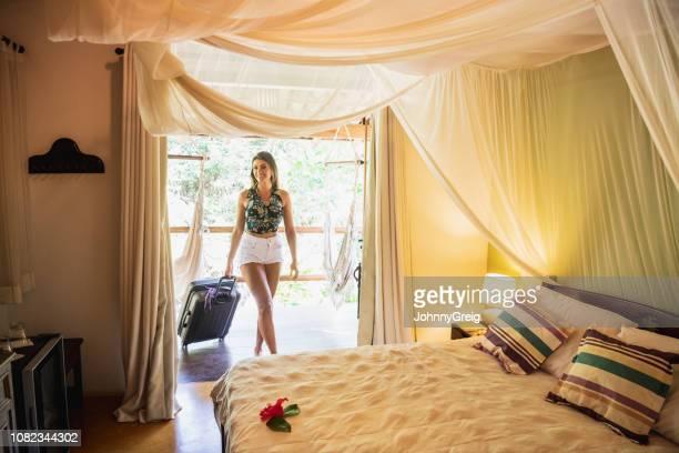 jovem mulher chegando em quarto de hotel - estação turística - fotografias e filmes do acervo