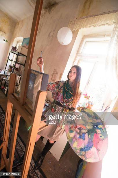 young woman artist doing paintings in her home studio - one young woman only stock pictures, royalty-free photos & images