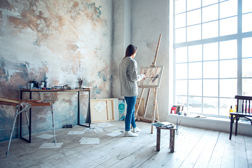 Young woman artist painting at home creative standing drawing 1143163619