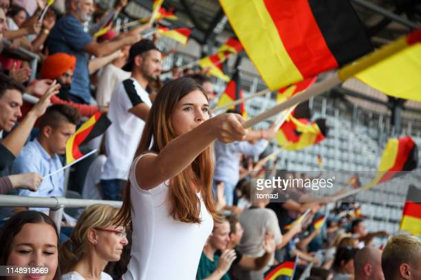 young woman as spectator on a stadium with german flags - world championship stock pictures, royalty-free photos & images