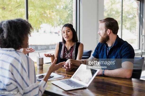 若い女性はカウンセリングセッション中に質問する - 銀行支店長 ストックフォトと画像
