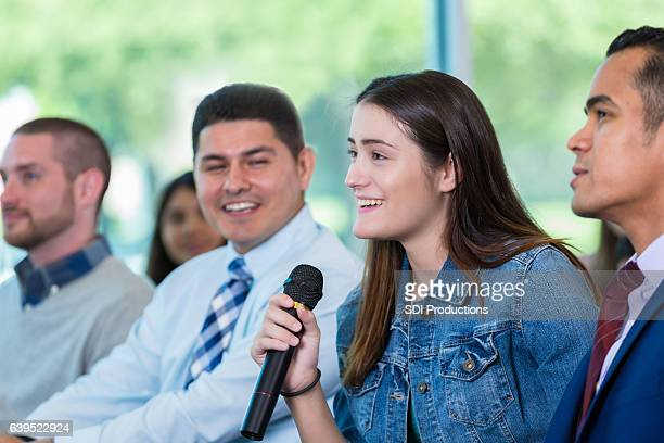 young woman asks question during town hall meeting - politik stock-fotos und bilder