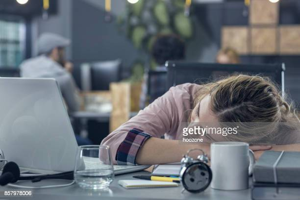 Jonge vrouw in slaap op het werk