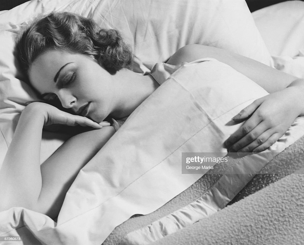 Young woman asleep in bed, (B&W), close-up : Stock Photo
