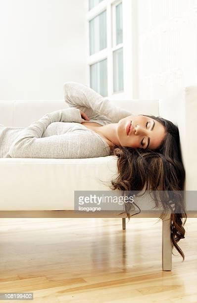 """Mujer joven en un sofá en el """"sleep mode"""","""