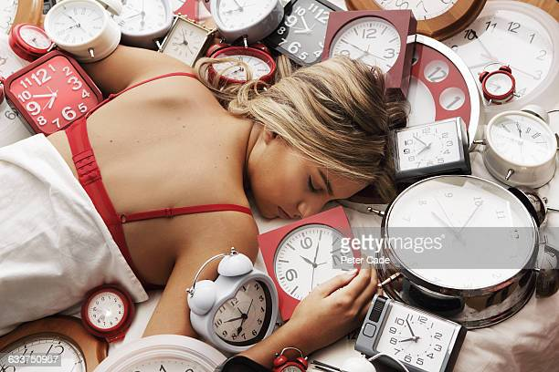 Young woman asleep on pile of clocks