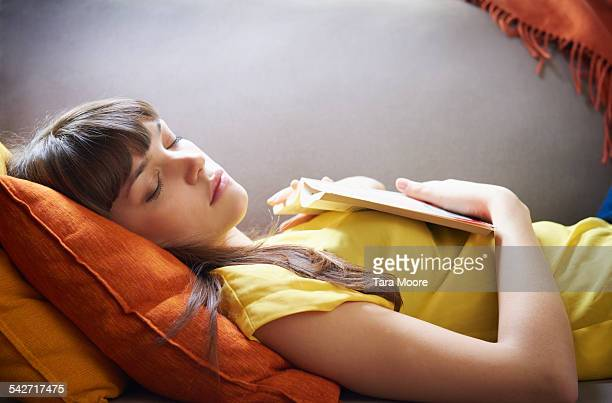 Young woman asleep with book on sofa
