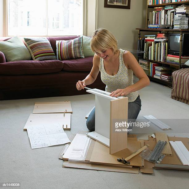 Young Woman Assembling Flatpack Furniture in Her Living Room