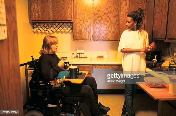 young woman assisting disabled woman in kitchen - philanthropist stock pictures, royalty-free photos & images