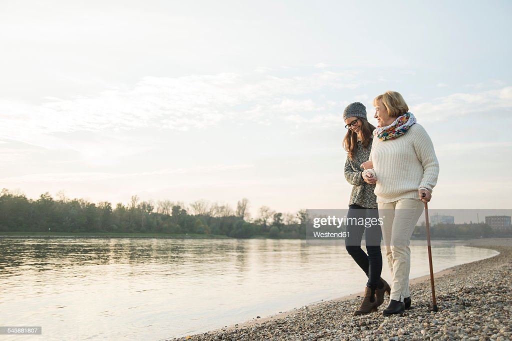 Young woman assisting her grandmother walking : Stock Photo