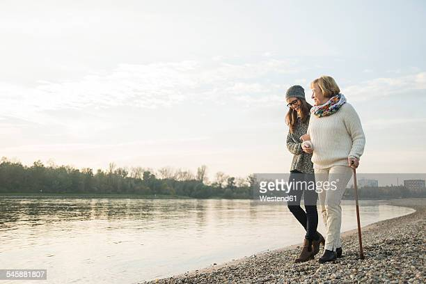 young woman assisting her grandmother walking - mithilfe stock-fotos und bilder