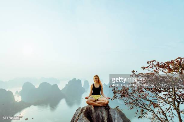 Young woman assumes yoga pose on rock summit, looks over sea