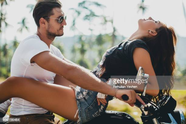 young woman astride boyfriend on motorcycle, krabi, thailand - woman straddling man stock pictures, royalty-free photos & images
