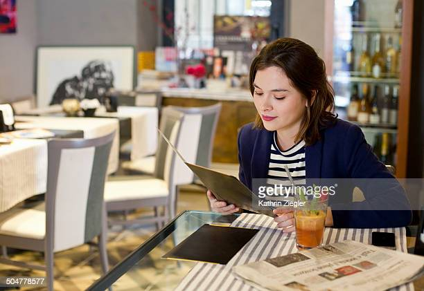 young woman at a café, choosing from menu