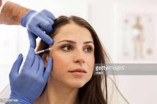 young woman at a cosmetologist's office - botox stock pictures, royalty-free photos & images