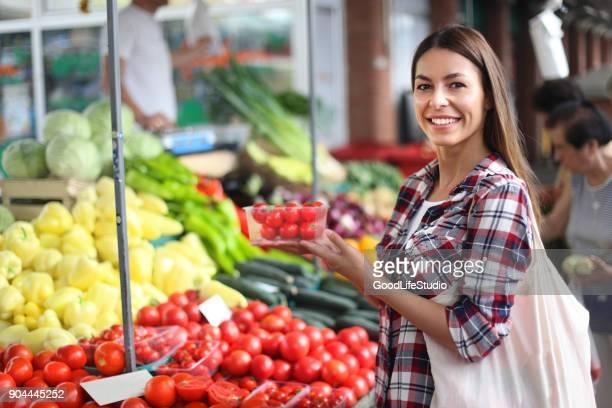 young woman at a farmer's market - bancarella di verdura foto e immagini stock