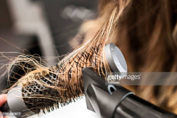 young woman at a hair salon ,hairdresser using hairdryer - blow drying hair stock pictures, royalty-free photos & images