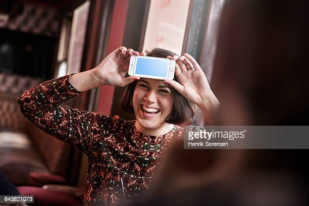 young woman at a pub with phone at her forehead