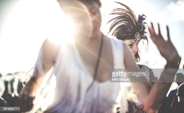 young woman at a summer music festival dancing among the crowd. - feather fan stock-fotos und bilder