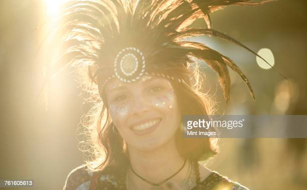 Young woman at a summer music festival wearing feather headdress and face painted, smiling at camera.