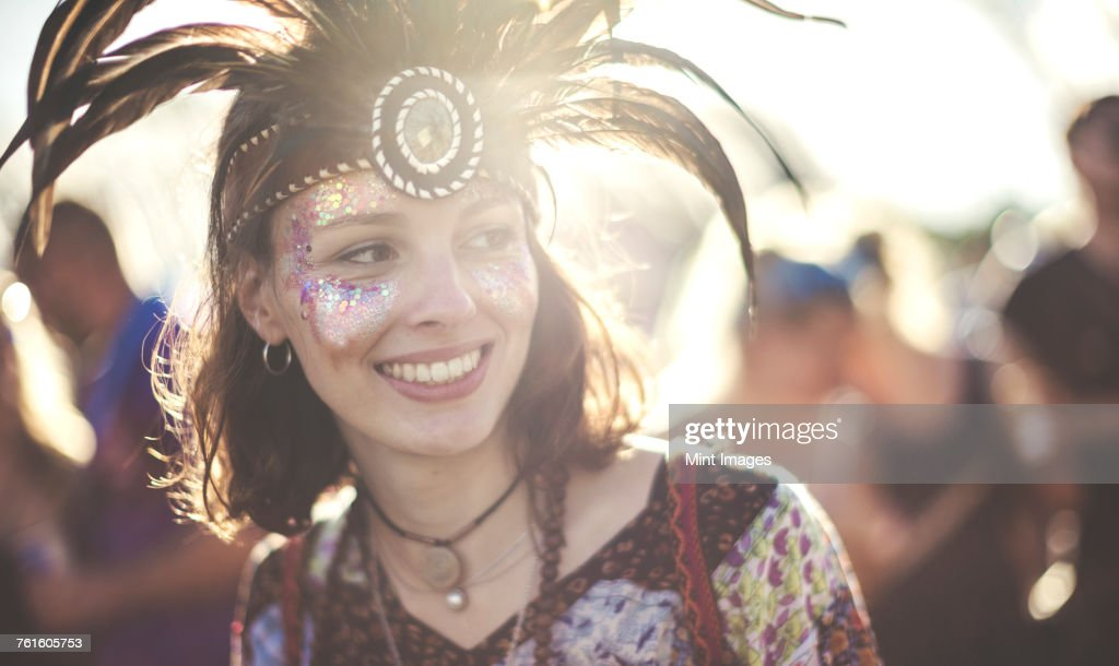 Young woman at a summer music festival wearing feather headdress and face painted, smiling. : Stock Photo
