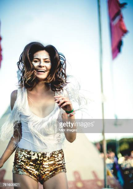 Young woman at a summer music festival wearing golden sequinned hot pants, face painted, smiling at camera.