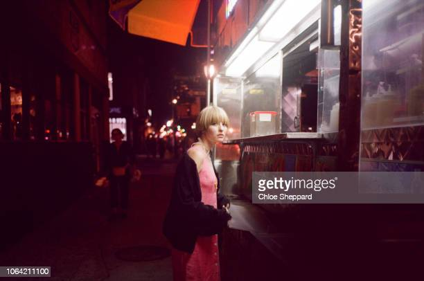 young woman at a take out stand at night in nyc - one night stand stock-fotos und bilder