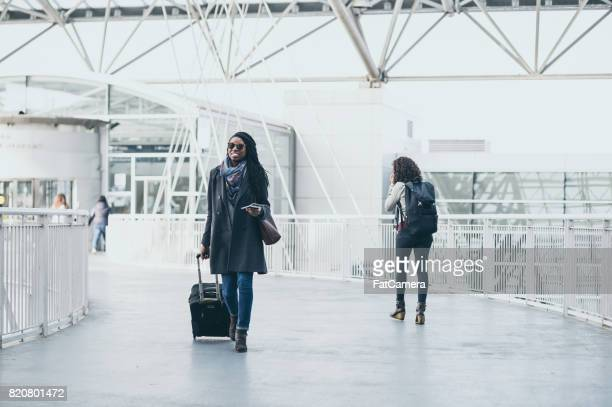 Young woman at airport pulling luggage