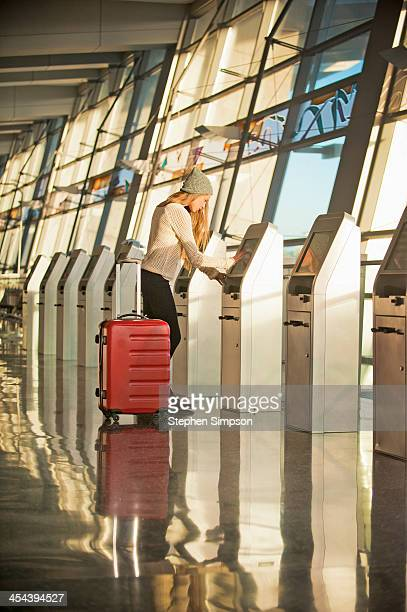 young woman at airport ticket machine