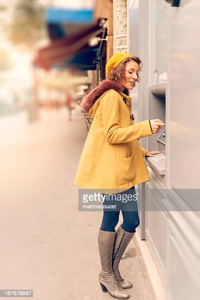 Young woman at ATM machine on street.