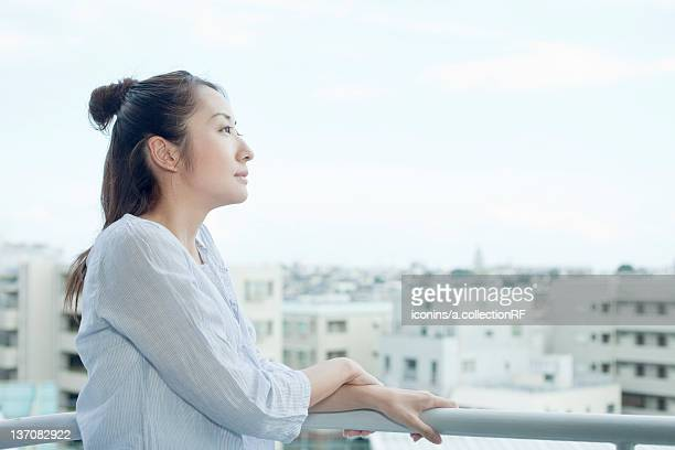 Young woman at balcony looking at cityscape, Tokyo Prefecture, Japan