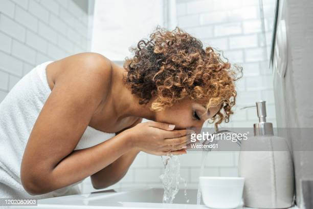 young woman at bathroom sink - washing face stock pictures, royalty-free photos & images
