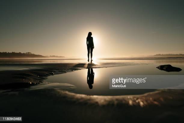 young woman at beach at sunset and her reflection - reflexo efeito de luz imagens e fotografias de stock
