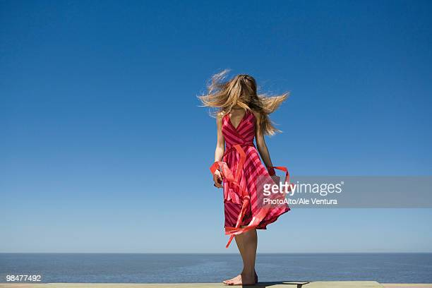 Young woman at beach enjoying sunshine, tossing hair