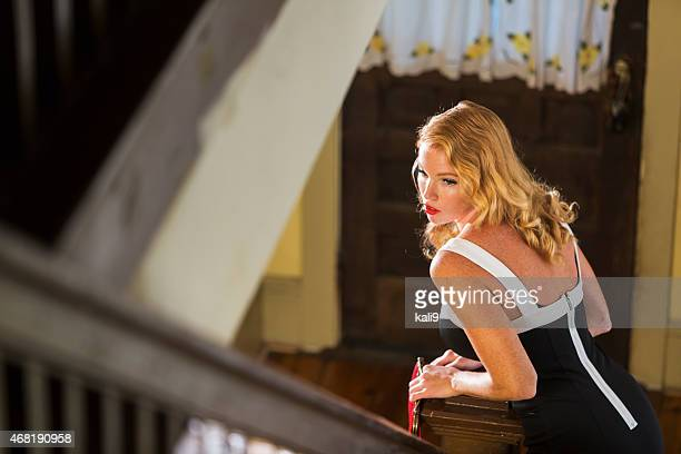 Young woman at bottom of stairs dressed for night out