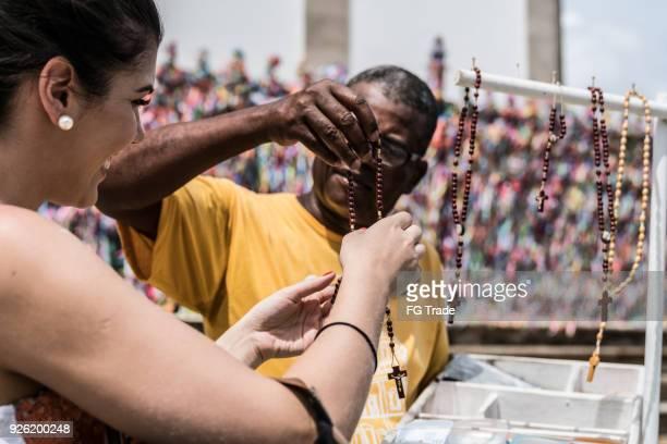 Jonge vrouw op het kruisbeeld op straatmarkt kopen
