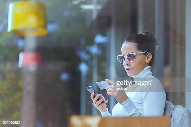 Jeune femme au café à l'aide de carte de crédit pour les transactions en ligne