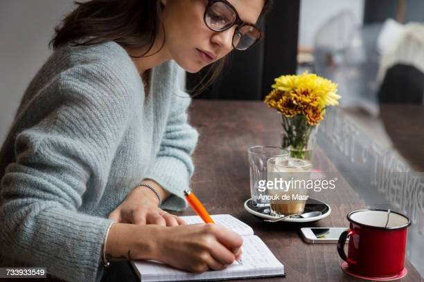Young woman at cafe window seat writing notes