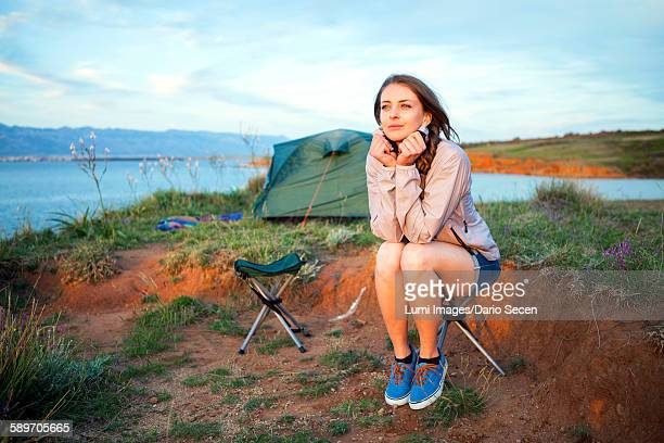 Young woman at campsite day dreaming