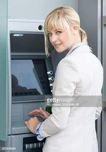 Young woman at cash dispenser