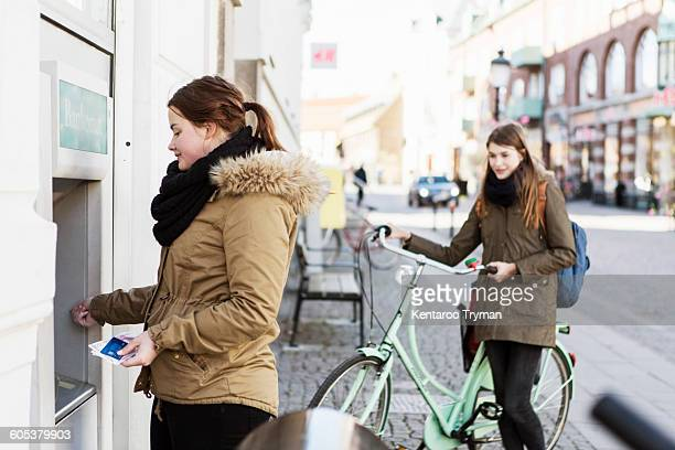 Young woman at cash machine with female friend in background