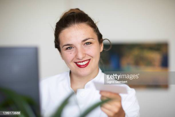 young woman at computer, handing over card - sigrid gombert stock pictures, royalty-free photos & images