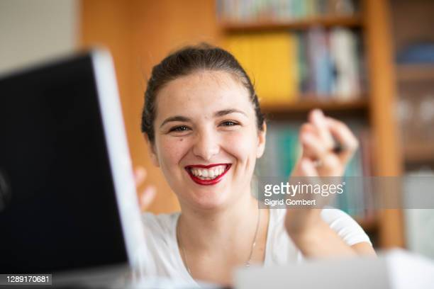 young woman at computer in library, smiling - sigrid gombert stock pictures, royalty-free photos & images