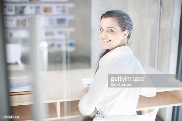 young woman at desk in creative office - femme brune de dos photos et images de collection