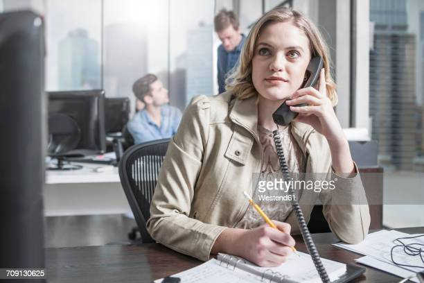 Young woman at desk in office on the phone