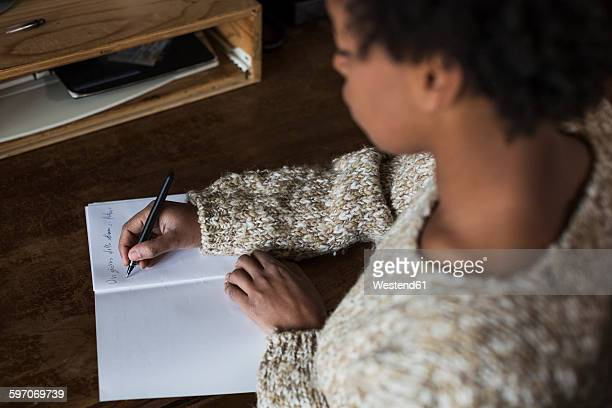 Young woman at desk writing in notebook