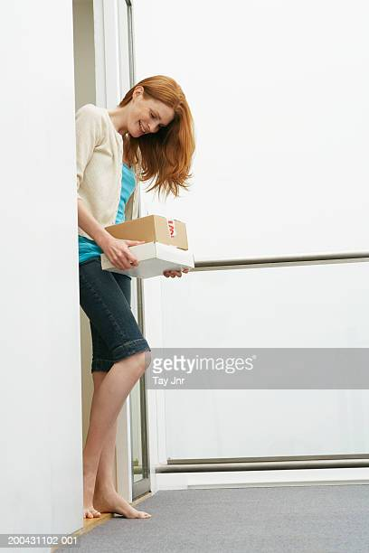 Young woman at front door holding parcels, smiling, side view