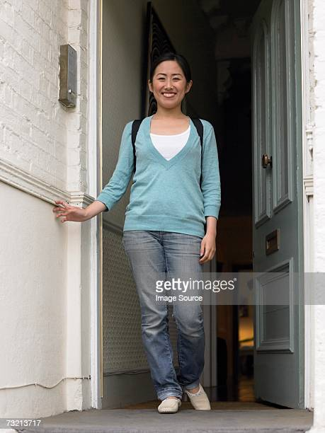 young woman at front door - doorway stock pictures, royalty-free photos & images
