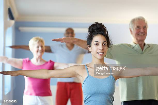 Young woman at front of fitness class.