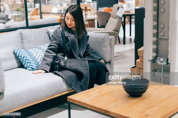 young woman at furniture store choosing sofa - furniture stock pictures, royalty-free photos & images